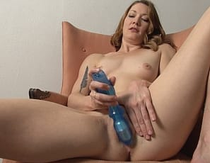 penetrating herself with a toy while she flexes her tattooed bicep